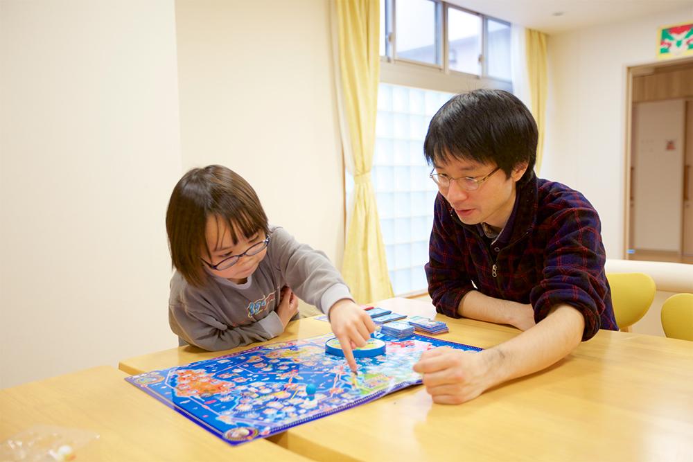 先生が利用者の女の子と一緒にボードゲームで遊んでいる様子。