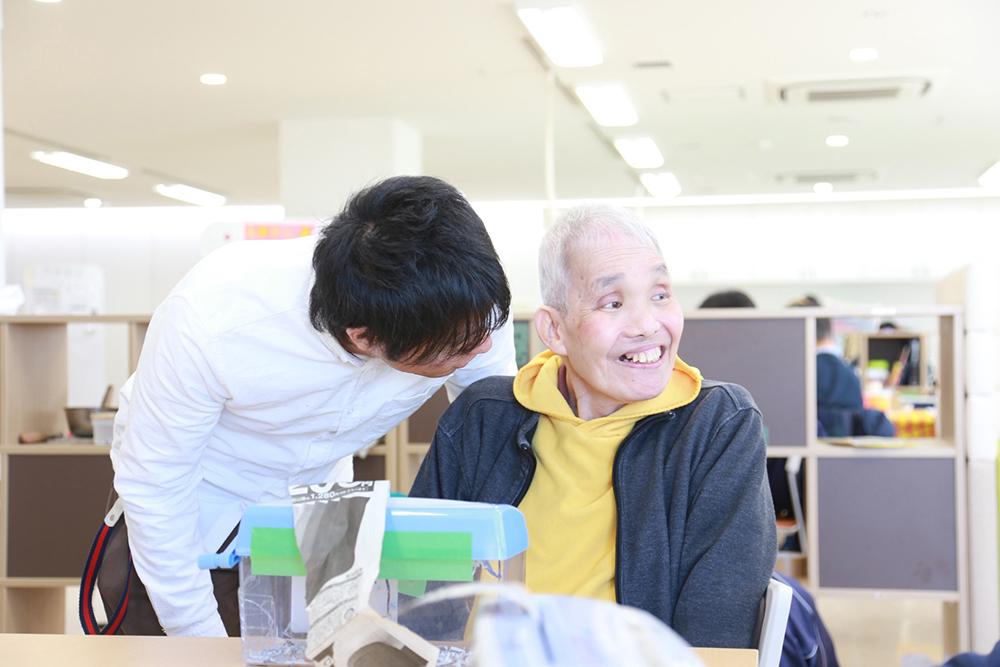 室内で施設の方が素敵な笑顔をしている利用者さんに話しかけている様子。