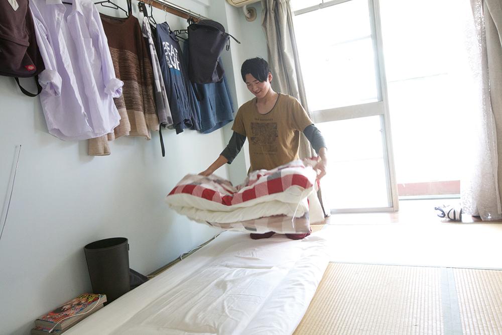 個室で、布団をたたんでいる様子。