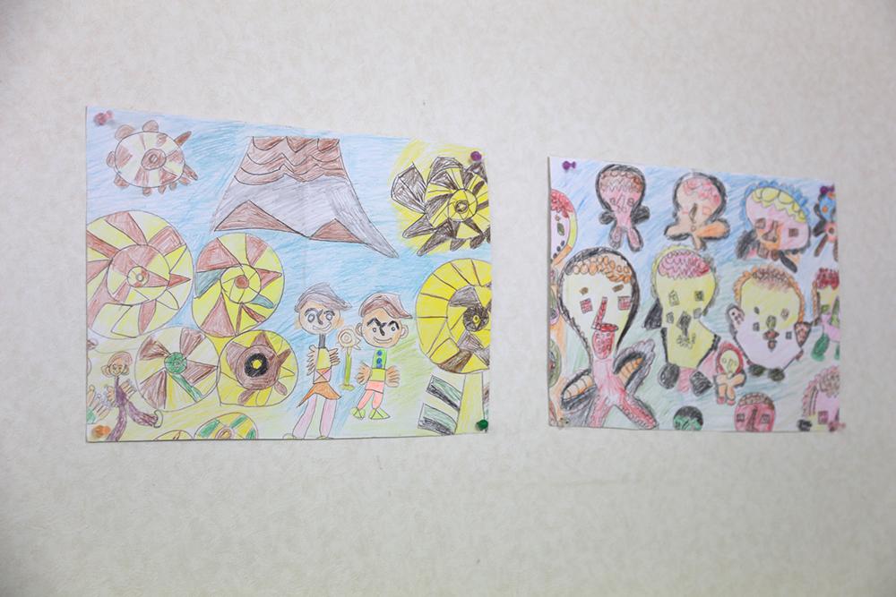 壁に貼られた色鉛筆で描かれた絵が二枚。