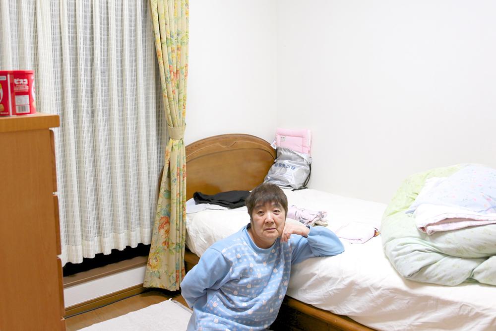 個室でゆったりベッドに肘を掛け、ポーズをとる利用者さん。