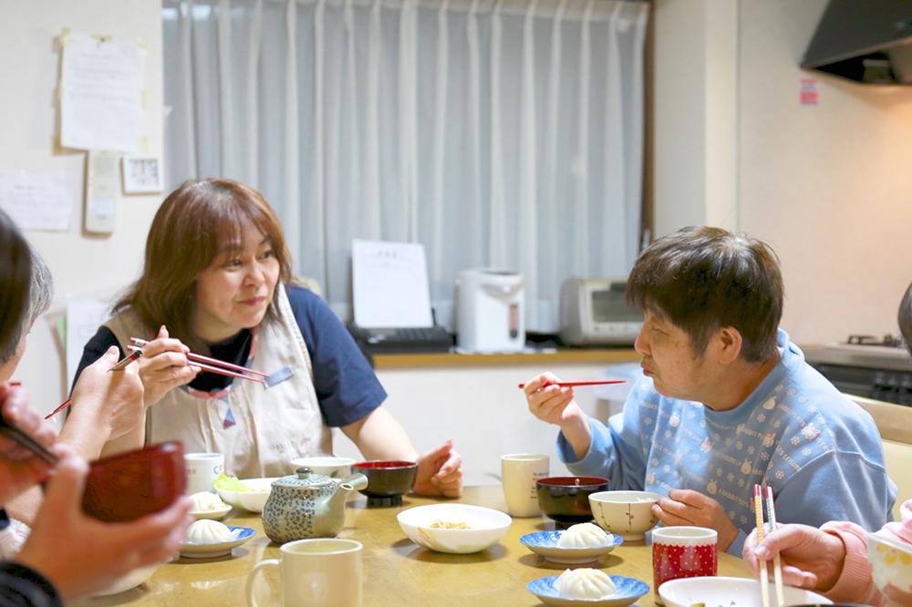 スタッフさんと利用者さんが楽しげに夕食を食べている様子。