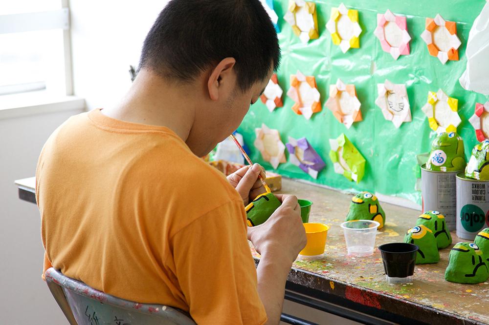 カエルの置物の製作中、色を施している利用者さん。
