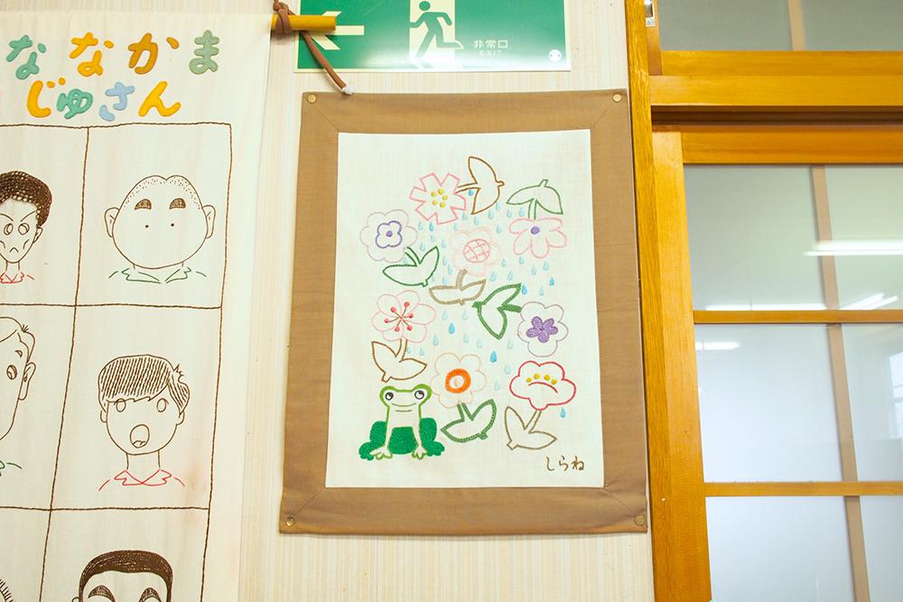 壁に貼られた、花やカエルのイラストが描かれた一枚。