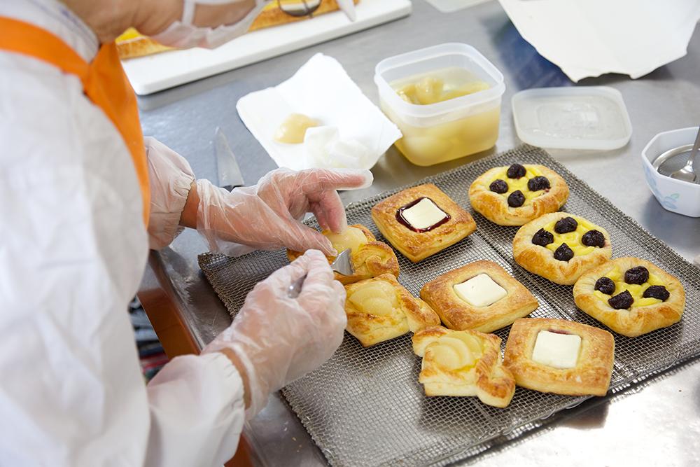 焼けたデニッシュに果物やチーズを乗せている様子。