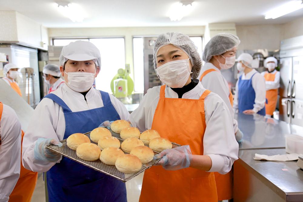 出来立てのパンの乗った板を持ってポーズをとる2人。