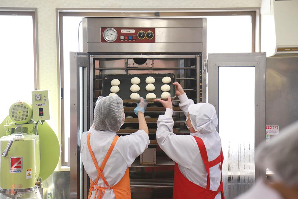 焼けたパンをオーブンから取り出して焼き色を確かめている2人。