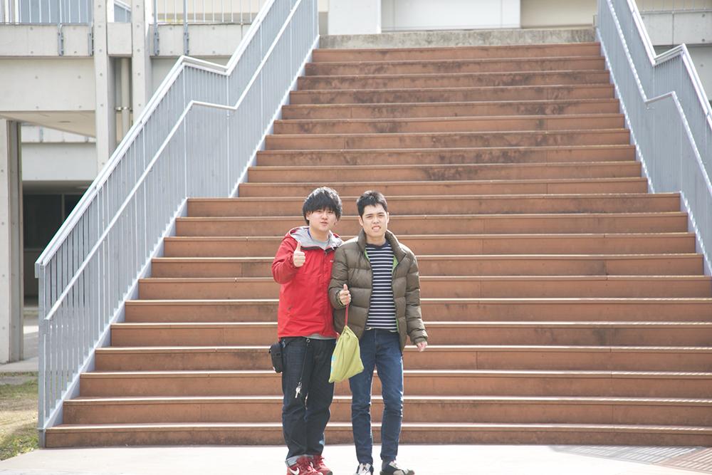 外の階段下でポーズをとる2人。
