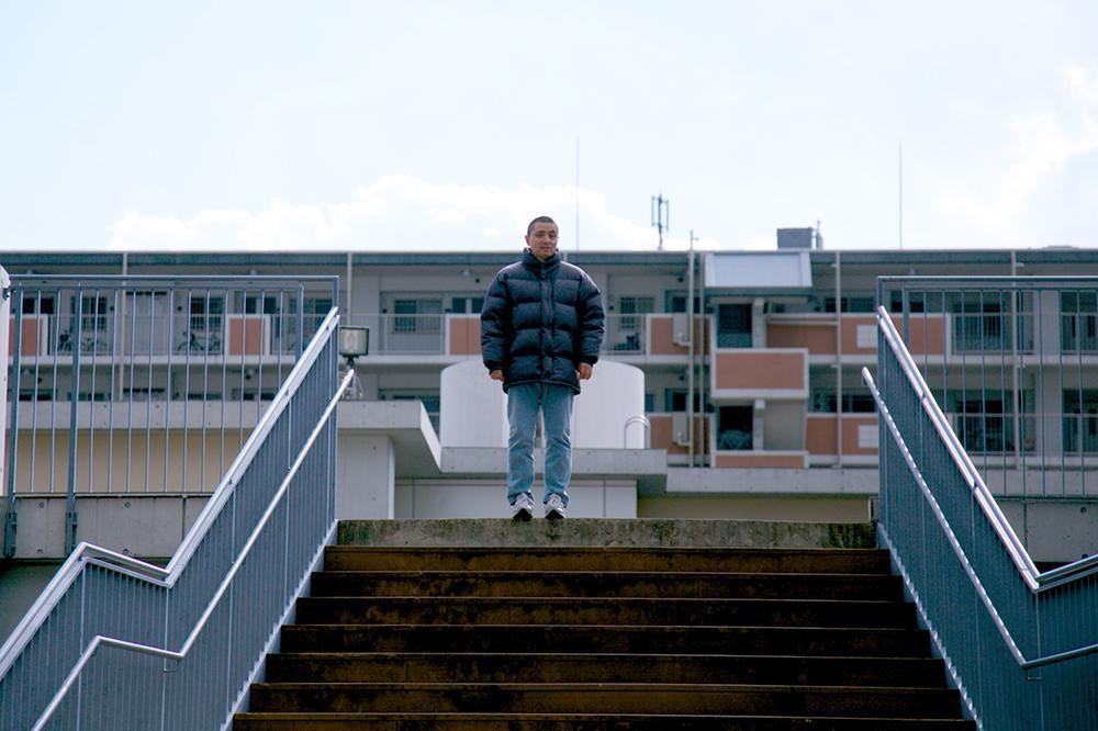 清々しい表情で外の階段の上からまっすぐ前をみている利用者さん。