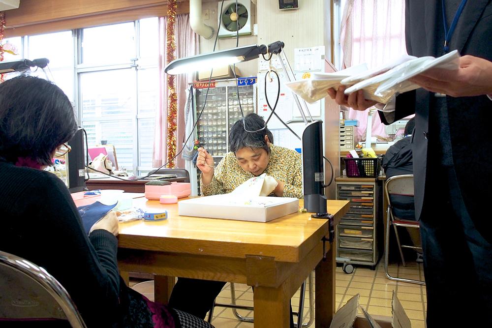 利用者さんが布を縫う作業をしている様子。
