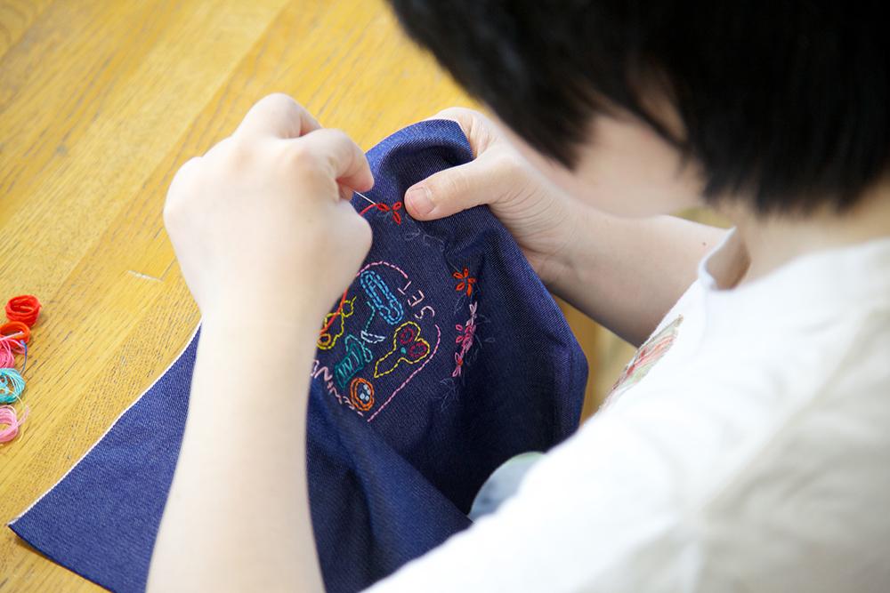 布に刺繍を施す利用者さんの様子。